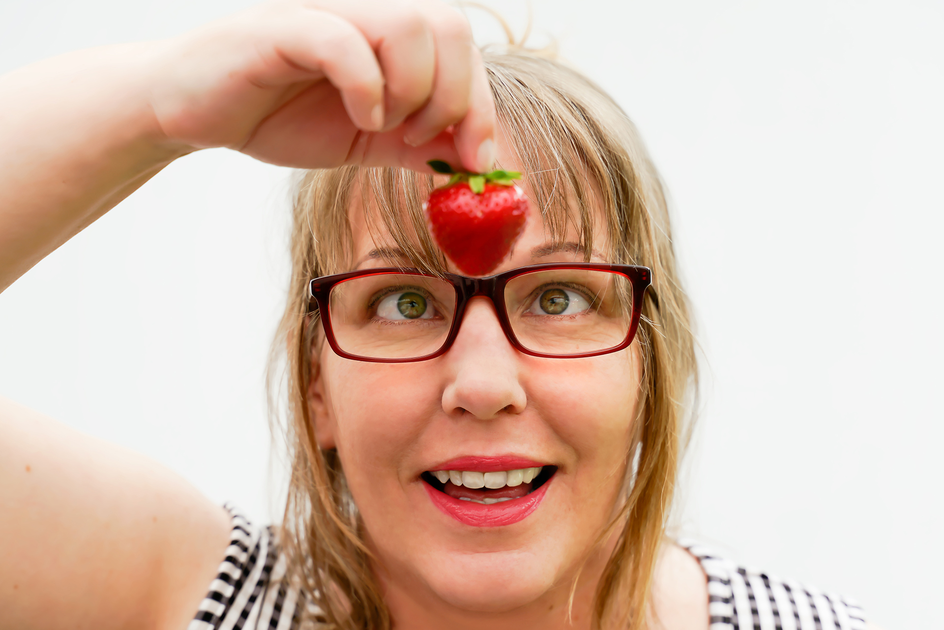 Blond woman holds up a strawberry