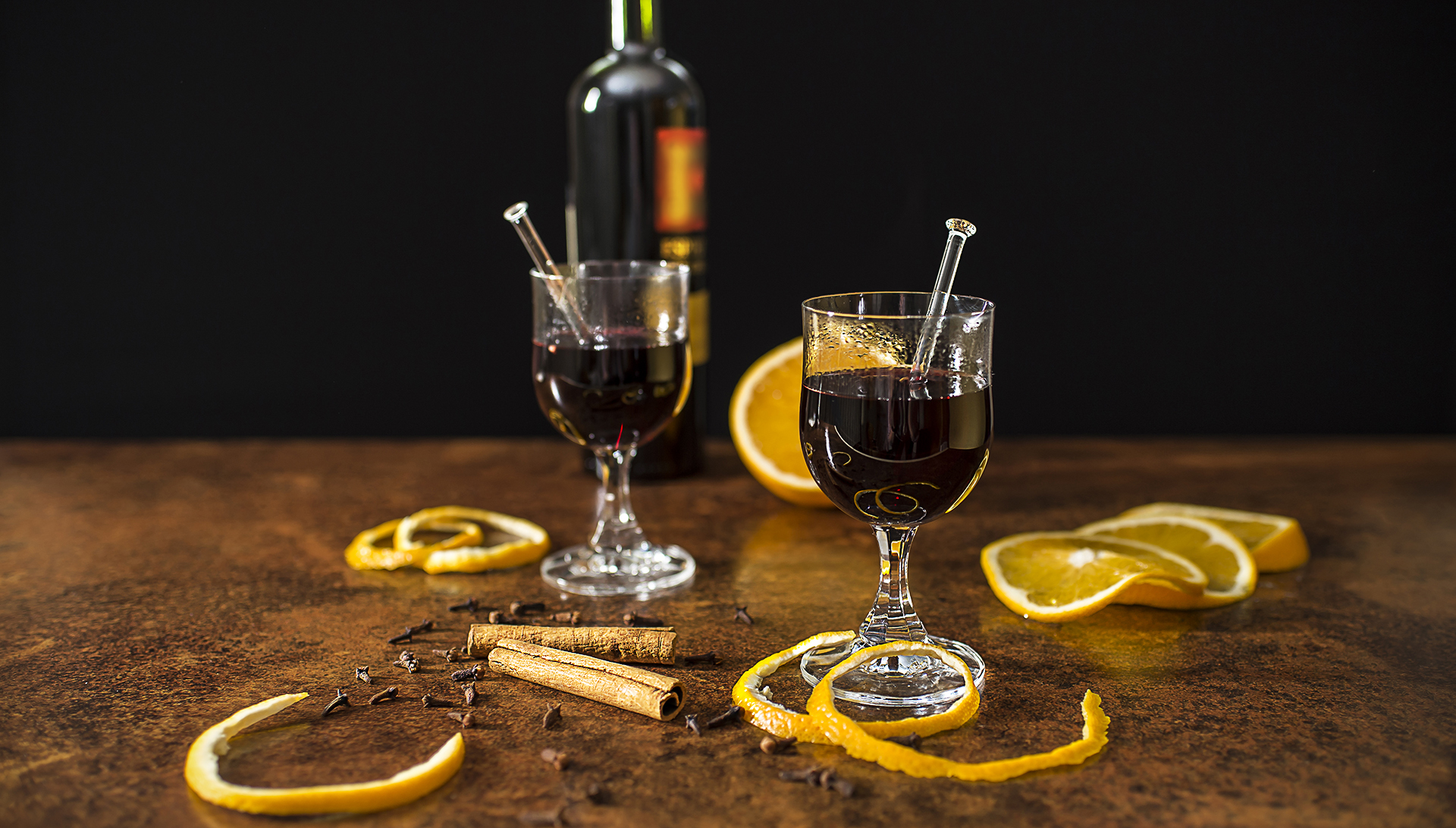 Mulled wine with spices and oranges close up in front of black background